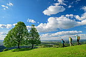 Three people hike towards Linden, Jusiberg, Swabian Alb, Baden-Württemberg, Germany