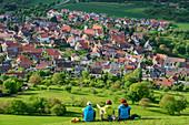 Three people sit in meadow and look at the village of Kohlberg, Jusiberg, Swabian Jura, Baden-Württemberg, Germany