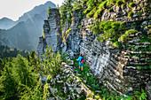 Woman hiking past banded rock wall, Schiara, Bellunesian Dolomites National Park, Dolomites, UNESCO World Heritage Dolomites, Veneto, Italy