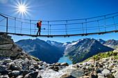 Frau geht auf Hängebrücke über Bach, Schlegeisspeicher und Großer Möseler im Hintergrund, Olpererhütte, Peter-Habeler-Runde, Zillertaler Alpen, Tirol, Österreich