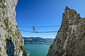 Frau geht auf Klettersteig über Hängebrücke, Klettersteig Drachenwand, Mondsee im Hintergrund, Drachenwand, Mondsee, Salzkammergut, Salzburg, Österreich