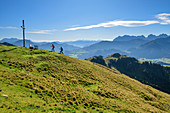 Two people hiking up to the summit cross, Kaisergebirge in the background, Wandberg, Chiemgau Alps, Tyrol, Austria