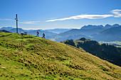 Zwei Personen beim Wandern steigen zu Gipfelkreuz auf, Kaisergebirge im Hintergrund, Wandberg, Chiemgauer Alpen, Tirol, Österreich