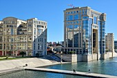 France, Herault, Montpellier, Port Marianne district, Athena footbridge, cyclists crossing the river Le Lez with the Hotel of Region in the background conceived by the architect ricardo Bofill