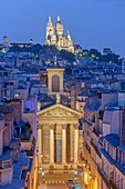 France, Paris, the Sacre Coeur basilica on the Montmartre hill and the Notre Dame de Lorette church illuminated at night
