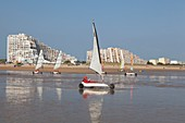 France, Vendee, Saint Jean de Monts, land sailing on the beach and seafront buildings in the background