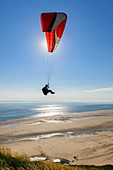 France, Manche, Barneville Carteret, a paraglider takes off from Cape Carteret and fly over the Old Church beach