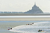 France, Manche, Mont Saint Michel bay, listed as World Heritage by UNESCO, kayaking against the tidal bore at Pointe du Grouin Sud, tidal phenomenon forming a wave at rising tide, Mont Saint Michel in the background