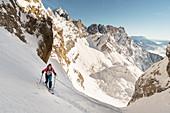 Skitourengeherin beim Aufstieg zur Roten Rinnscharte mit Aussicht auf den Wilden Kaiser, Tirol, Österreich