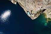 Junge Frau klettert an einer steilen Granitkante über dem Lac de Capitello, Restonica, Korsika