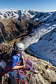 Kletterin blickt am Standplatz in das leicht verschneite, hochalpine Gelände der Zillertaler Alpen, Gigalitz, Tirol, Österreich