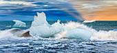 Eisberge vor der Küste Islands im Abendlich, aufspritzendes Wasser, Diamond Beach, Jökulsárlón, Island