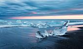 Vom Meer angespülte Eisbrocken am schwarzen Diamond Beach im Abendlicht, Jökulsárlón, Island