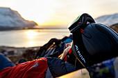 Skifahrerin liegt im Gras und genießt die letzten Sonnenstrahlen des Tages, Westfjorde, Island