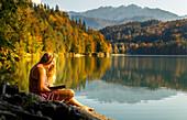 Junge Frau liest in einem Buch am herbstlichen Hechtsee, Kufstein, Tirol, Österreich