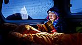 Junge Frau in Daunenjacke und Schlafsack sitzt bei Schlechtwetter im Auto und liest ein Buch im Schein der Stirnlampe, Dalvík, Island