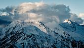 Dramatische Wolkenstimmung über verschneiten Stubaier Alpen, Tirol, Österreich