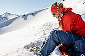 Junge Frau sitzt im Schnee und schließt ihre Skischuhe für die Abfahrt, Tröllaskagi, Island