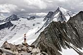 Trailrunner steht in hochalpiner Landschaft auf einem Grat, Schönbichler Horn, Schlegeis, Zillertaler Alpen, Tirol, Österreich