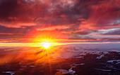 Mitternachtssonne scheint durch Nebelschwaden und bringt den Himmel zum Erleuchten, Isländisches Hochland
