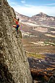 Junge Frau klettert auf plattigem Fels in Calvi, Korsika