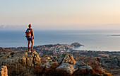 Junge Frau steht im Morgenlicht auf einem Felsen und blickt über die Stadt Calvi und die Westküste Korsikas