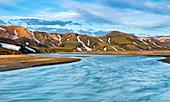 Langzeitbelichtung eines Flusses vor grün, gelben Hügeln, Landmannalaugar, Island