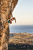 Junge Frau klettert an einer überhängenden Felswand mit dem Meer im Hintergrund, Conca, Korsika