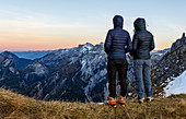 Two women in down jackets stand on the mountain and look at the Karwendel Mountains in the evening light, Gramai, Tyrol, Austria