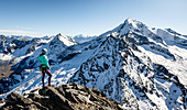 Young woman stands at the summit of the Gigalitz and looks at the high alpine landscape of the Großer Löffler, Zillertal Alps, Tyrol, Austria, which is lightly snowed in autumn