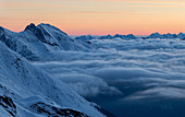 Dawn over wintry high mountain landscape with sea of clouds, Zischgeles, Sellrain, Tyrol, Austria