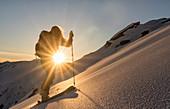 Young ski tourer sprints through an untouched slope in the warm morning sun, Zischgeles, Sellrain, Tyrol, Austria