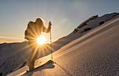 Junge Skitourengeherin spurt durch einen unberührten Hang in warmer Morgensonne, Zischgeles, Sellrain, Tirol, Österreich