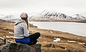 Young woman sits on stone and looks out into lightly snowed Icelandic landscape, Iceland