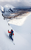 Skier on a steep slope with changing weather in the Westfjords, Iceland
