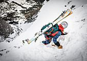 Ski alpinist descending with pimples and crampons in rocky terrain, Mieminger chain, Tyrol, Austria
