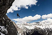 Alpinist rappels off an overhanging rock face with a ski on his backpack, Mieminger chain, Tyrol, Austria