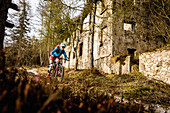 Young woman rides a mountain bike past a ruin, Lake Idro, Italy