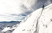 Ski tourer pulls a steep ascent trail past a change towards summit ridge, Alpbach valley, Tyrol, Austria