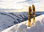 A pair of skis are in the snow in front of a wintry high mountain landscape, Tyrol, Austria