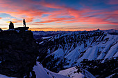 Silhouette of a climber on rocky outcrop at colorful sunset over wintry mountain landscape, Vals Valley, Tyrol, Austria