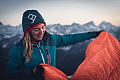 Young blonde woman prepares her bivouac sack in the evening light, Karwendel, Tyrol, Austria
