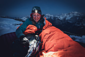 Young woman sits upright in her sleeping bag and takes something out of her backpack in the light of her headlamp, Karwendel, Tyrol, Austria