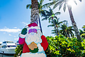 A Santa Claus figure under palm trees in the back light, Fort Myers Beach, Florida, USA