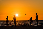 American football on the beach from the Gulf of Mexico at sunset, Fort Myers Beach, Florida, USA