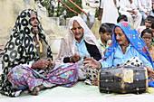 2015, Nandgoan / Nandagram, Vrindavan, Uttar Pradesh, India, Older women make music with billanga (drum) and karatals (cymbals) at a school event