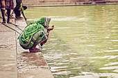 2017, Radhakund, Vrindavan, Uttar Pradesh, India, woman drinks the holy water of Radhakund