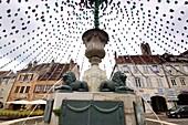 Flag ring over a monument to the center on the Place de la Liberté, Arbois, Jura, Franche Comté, Eastern France