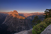 Half Dome in Yosemite National Park lit up in summer sunset, moon on the horizon, USA