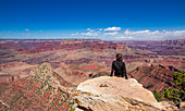 Man sitting on rock on the south rim of the Grand Canyon at sun with a blue sky, USA